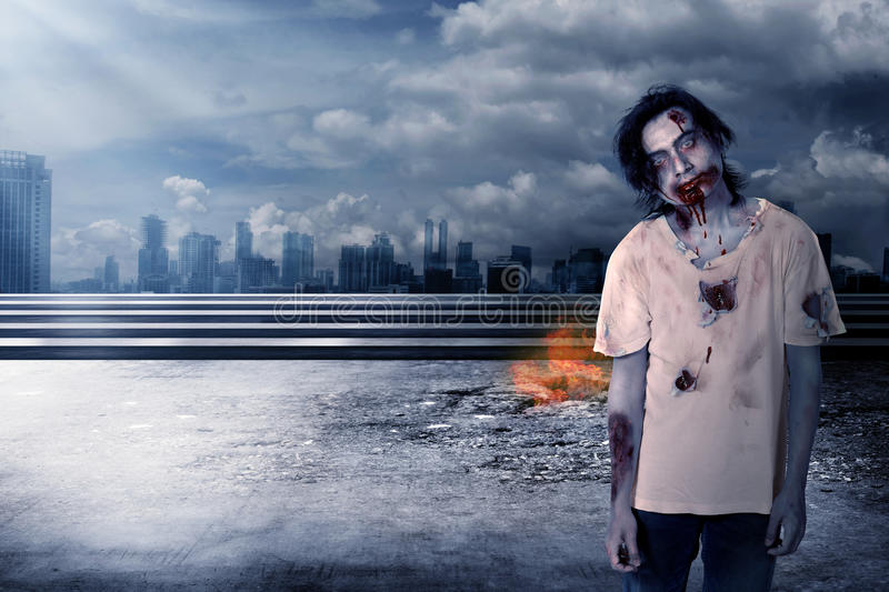 Creepy male zombie in the city. That on fire royalty free stock photos