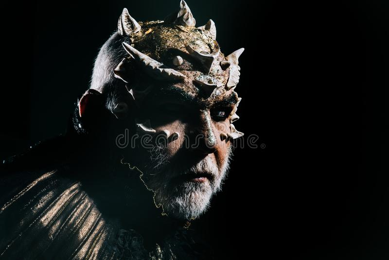 Creepy monster face illuminated by moonlight, scary night, supernatural concept. Demon head with sharp thorns and white. Beard on black background royalty free stock images