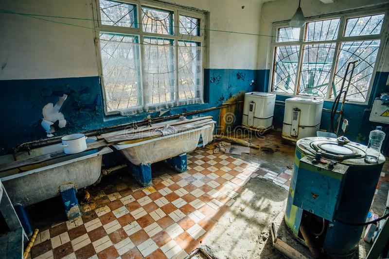 Creepy old laundry room with a dirty floor and broken wash machines and bathes in an abandoned psychiatric hospital. stock photos