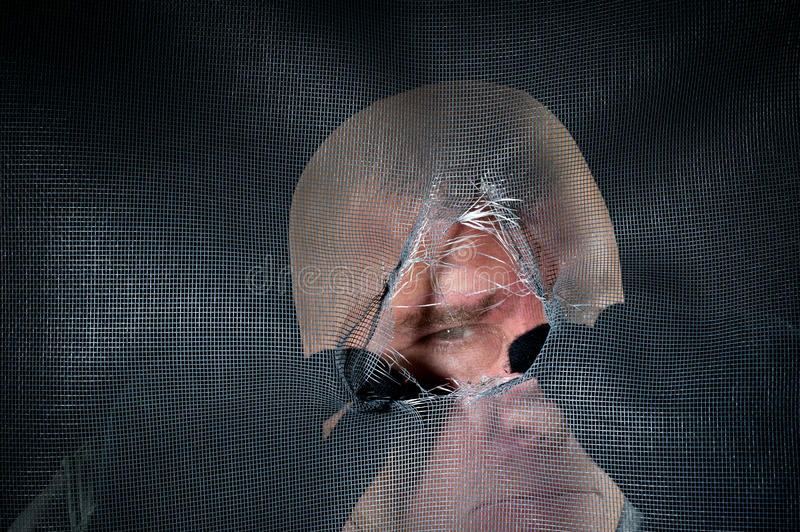 Creepy peeping tom. A peeping tom looking through a torn window screen in a creepy moment stock photos