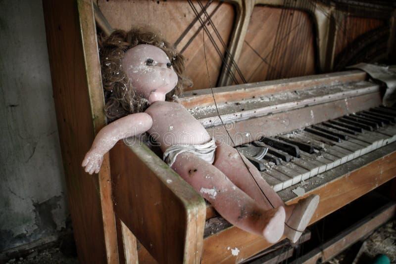 Creepy-Puppe auf einem Klavier in einem verlassenen Gebäude in Pripyat, Ukraine, Standort der nuklearen Desaster von Tschernobyl  lizenzfreies stockfoto