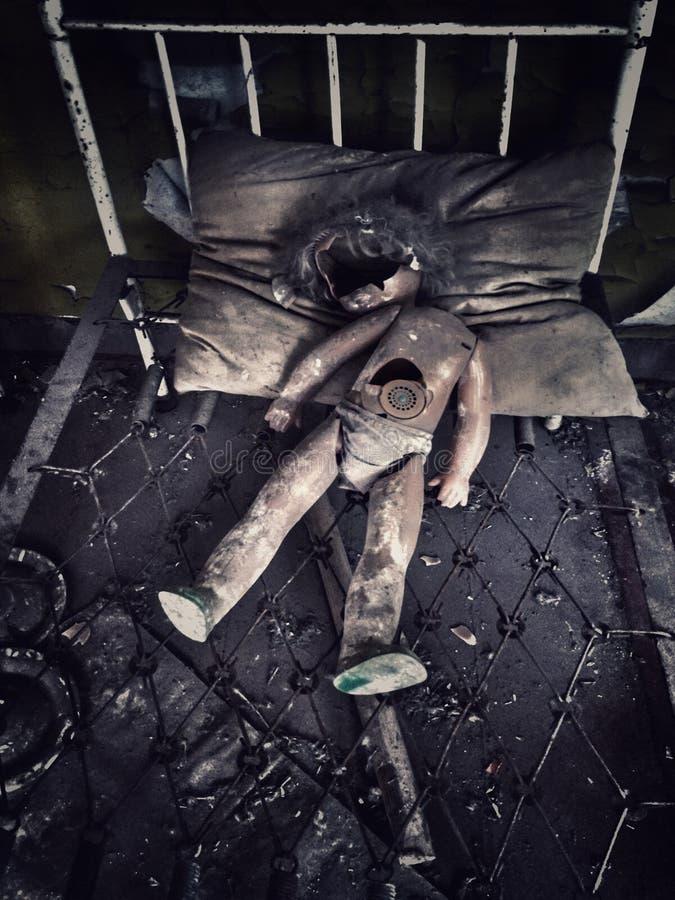 Creepy-Puppe mit gebrochenem Gesicht auf einem Bett in einem verlassenen Gebäude in Pripyat, Ukraine, in der Sperrzone von Tscher lizenzfreie stockbilder