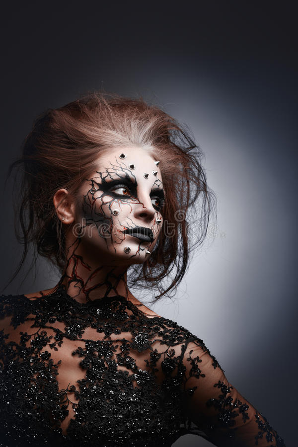 Creepy queen. A girl posing in a creepy halloween costume of a witch with peircing and cracked painted face stock image