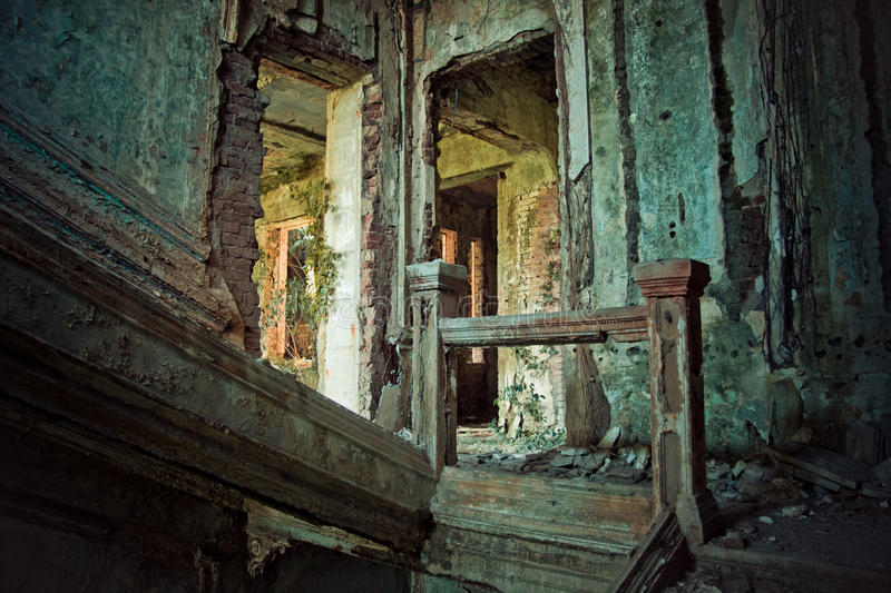 Creepy ruined and overgrown by plants interior of old mansion. Life after humanity post-apocalyptic concept stock photo