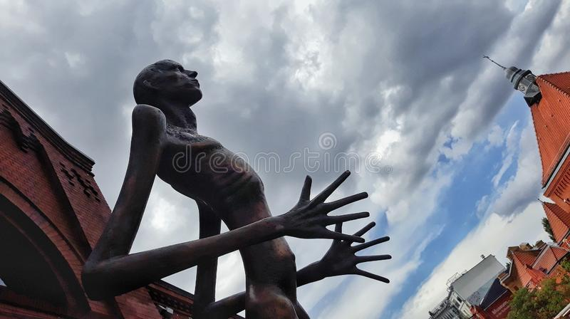 Creepy sculpture at the culture brewery in Prenzlauer Berg in front of a dramatic sky. stock photos