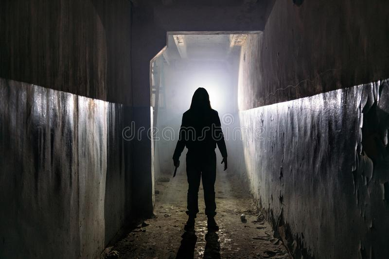 Creepy silhouette of unknown man with knife in dark abandoned building. Horror about maniac concept stock photos