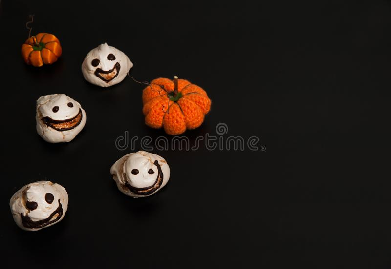 Creepy Smiley Ghost of Meringue, dekorative handgefertigte Kürbisse auf schwarzem Hintergrund stockbilder