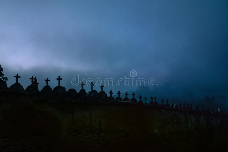 Creepy spooky graveyard atmosphere in the cemetery with tombstone and crosses in the foggy night royalty free stock images