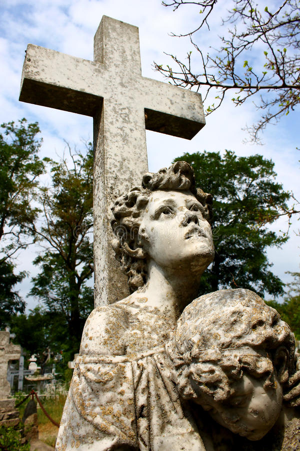 Creepy stone cross with statue in the cemetery. Creepy old stone cross with children statues in a cemetery from Danube Delta, Romania, covered by lichens royalty free stock image