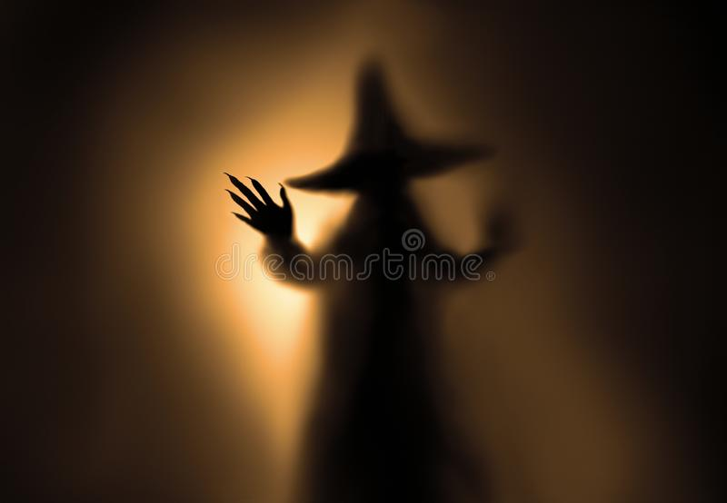 Creepy witch silhouette. Creepy witch silhouette behind a frozen glass and in the mist with backlit royalty free stock photos