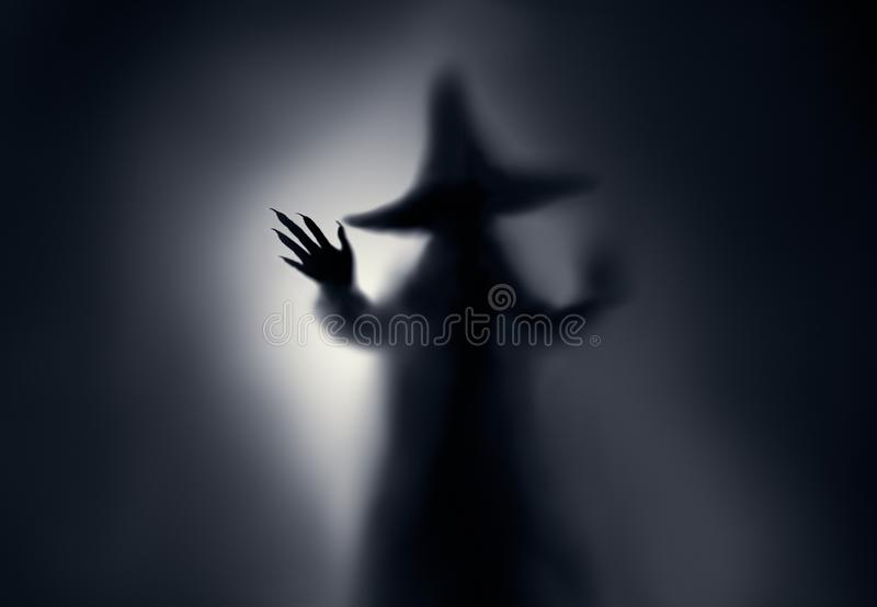 Creepy witch silhouette. Creepy witch silhouette behind a frozen glass and in the mist with backlit royalty free stock images