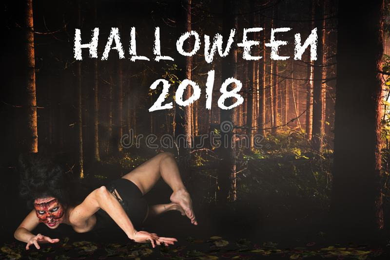 Creepy woman missing face in the forest and the message `Halloween 2018`. Creepy woman with missing face in the forest and the message `Halloween 2018 royalty free stock image