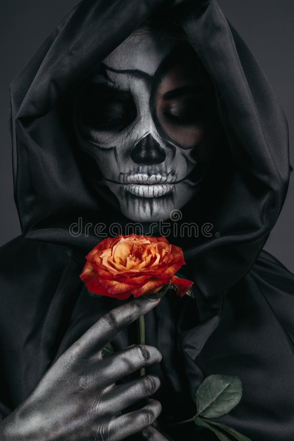 Terrifying female with skull face and red flower stock photos