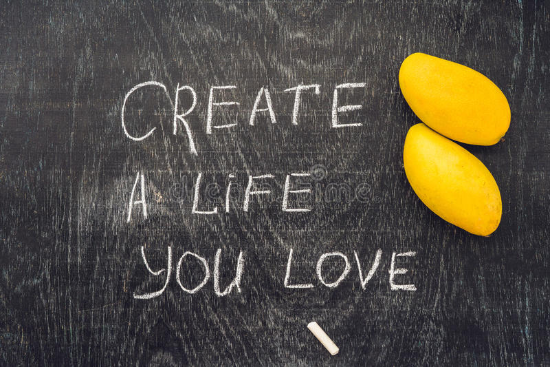 Crei la vita che amate il consiglio motivazionale - mandi un sms a su una lavagna dell'ardesia con gesso fotografie stock libere da diritti