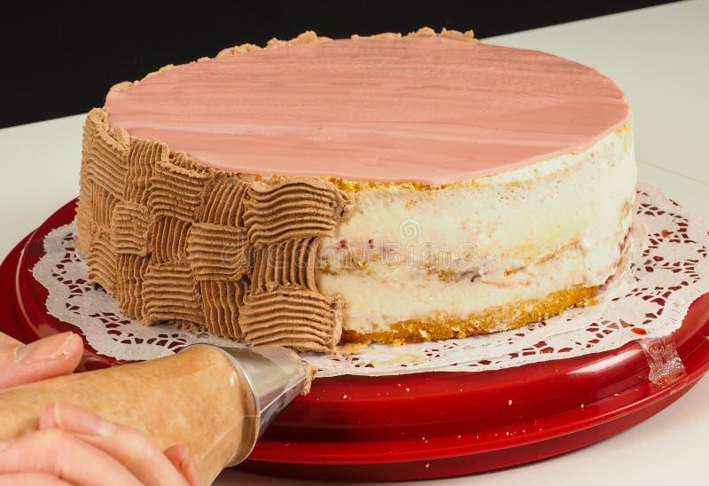 Crema aflautada del chocolate del panadero profesional de la torta sobre la torta fotografía de archivo libre de regalías