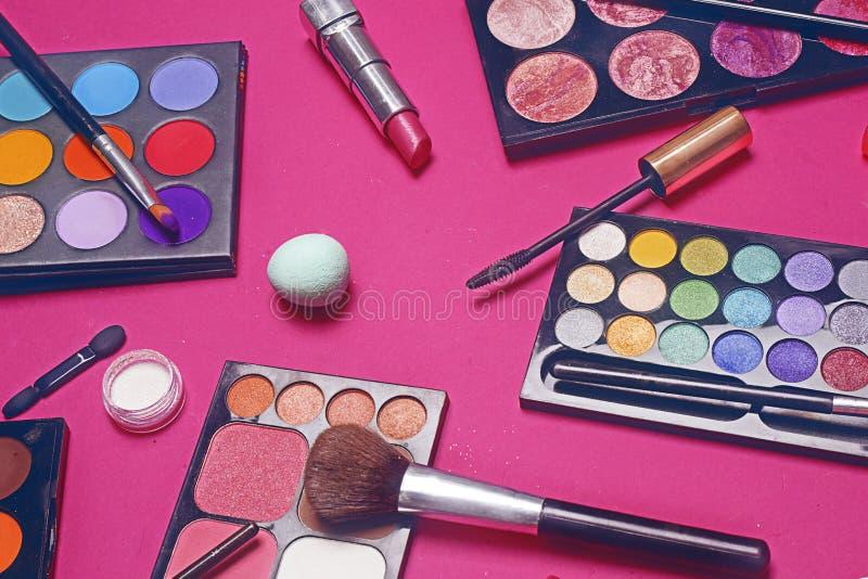 Crema, barra de labios, polvo, rimel y cepillos Sombras para un maquillaje, esponjas, lustre Los cosméticos de las mujeres en un  foto de archivo