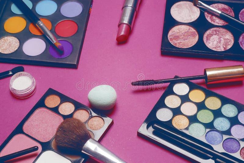 Crema, barra de labios, polvo, rimel y cepillos Sombras para un maquillaje, esponjas, lustre Los cosméticos de las mujeres en un  fotos de archivo