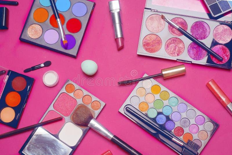Crema, barra de labios, polvo, rimel y cepillos Sombras para un maquillaje, esponjas, lustre Los cosméticos de las mujeres en un  imagenes de archivo