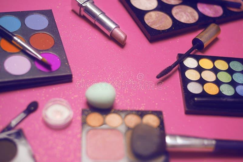 Crema, barra de labios, polvo, rimel y cepillos Sombras para un maquillaje, esponjas, lustre Los cosméticos de las mujeres en un  fotografía de archivo