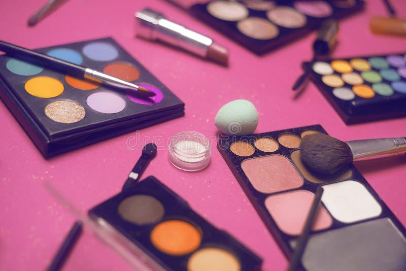 Crema, barra de labios, polvo, rimel y cepillos Sombras para un maquillaje, esponjas, lustre Los cosméticos de las mujeres en un  foto de archivo libre de regalías
