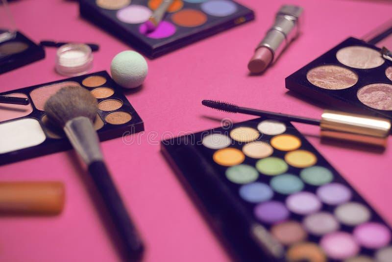 Crema, barra de labios, polvo, rimel y cepillos Sombras para un maquillaje, esponjas, lustre Los cosméticos de las mujeres en un  fotos de archivo libres de regalías