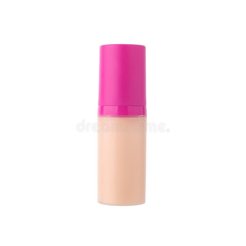 Crema beige della bottiglia di vetro del fondamento del fronte con il cappuccio rosa di plastica sul primo piano isolato fondo bi fotografia stock