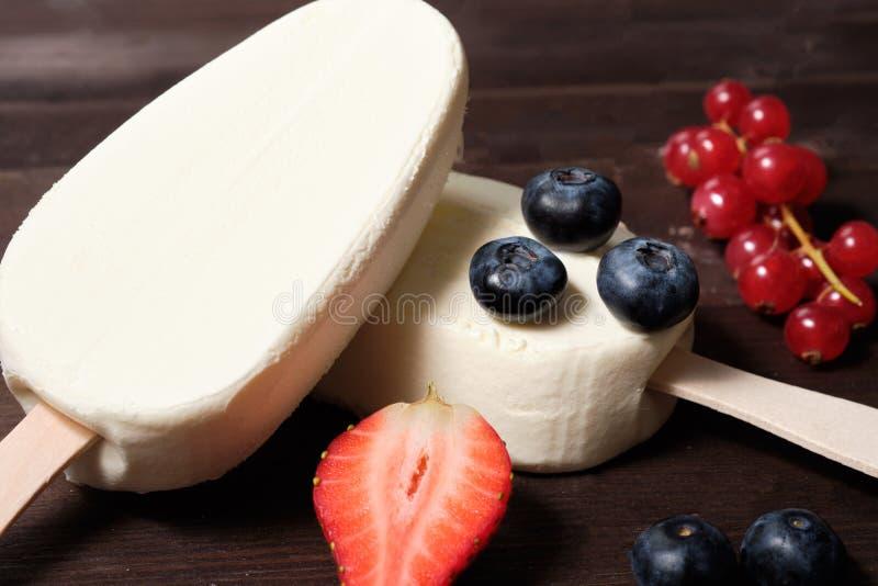 Crema bianca del gelato alla crema su un bastone con le fragole, i mirtilli ed il ribes rosso sui precedenti di legno del dack fotografia stock libera da diritti