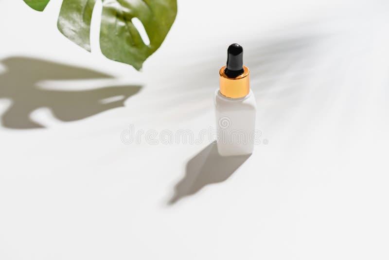 Crema blanca de la botella del suero, maqueta de la marca de producto de belleza Opini?n superior sobre el fondo blanco fotos de archivo