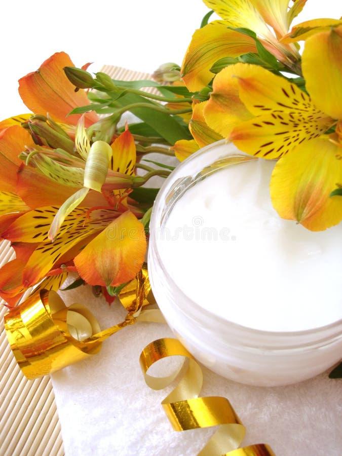 Crema cosmética con las flores fotografía de archivo