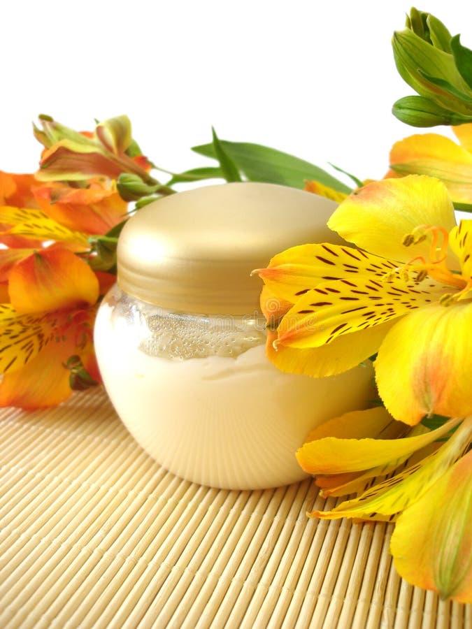 Crema cosmética con las flores fotografía de archivo libre de regalías