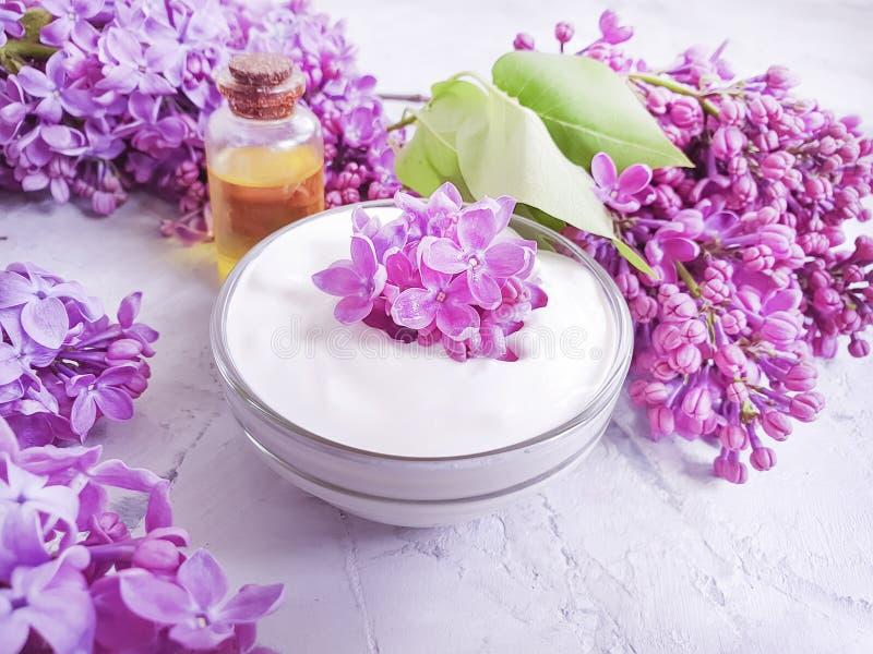 Crema cosm?tica, flor de la lila del aceite del extracto de la relajaci?n del verano en un fondo concreto gris foto de archivo libre de regalías