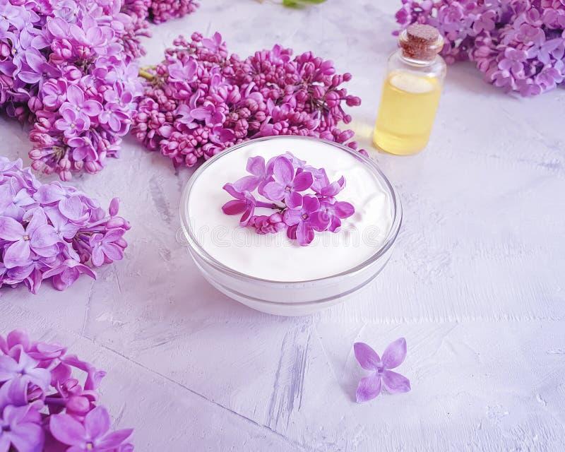 Crema cosm?tica, flor de la lila del aceite del extracto del verano en un fondo concreto gris fotografía de archivo
