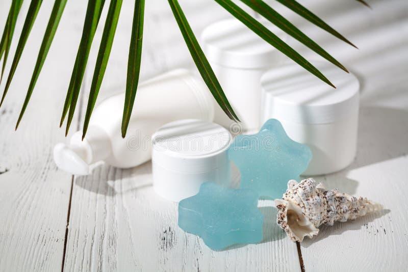 Crema cosmética y envases hermosos del balneario en la tabla blanca foto de archivo