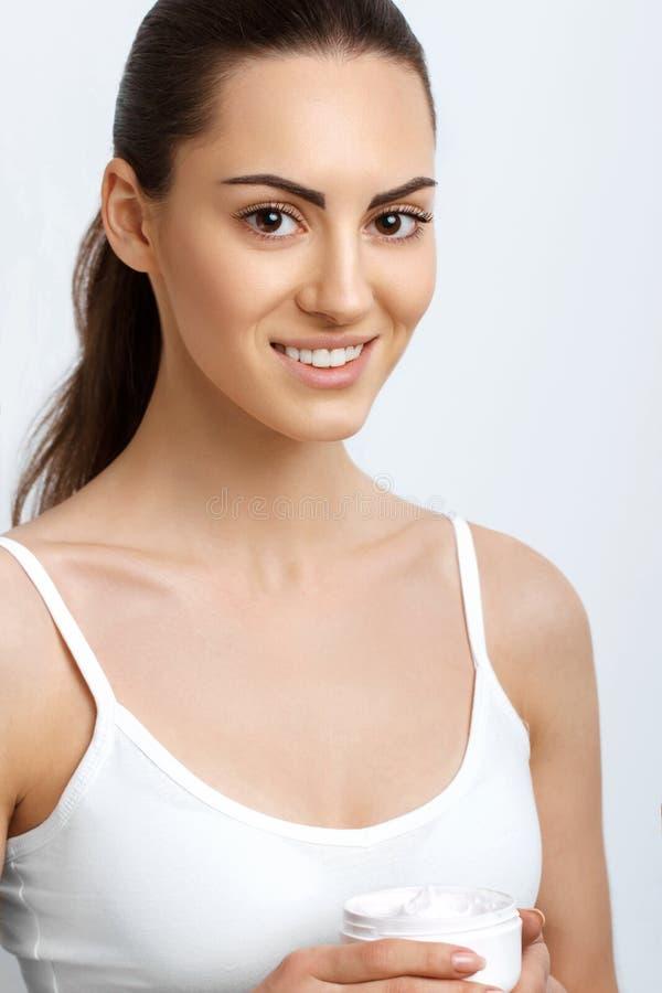 Crema cosmetica della tenuta della donna Skincare del fronte Crema d'applicazione femminile e sorridere Trucco naturale fotografia stock