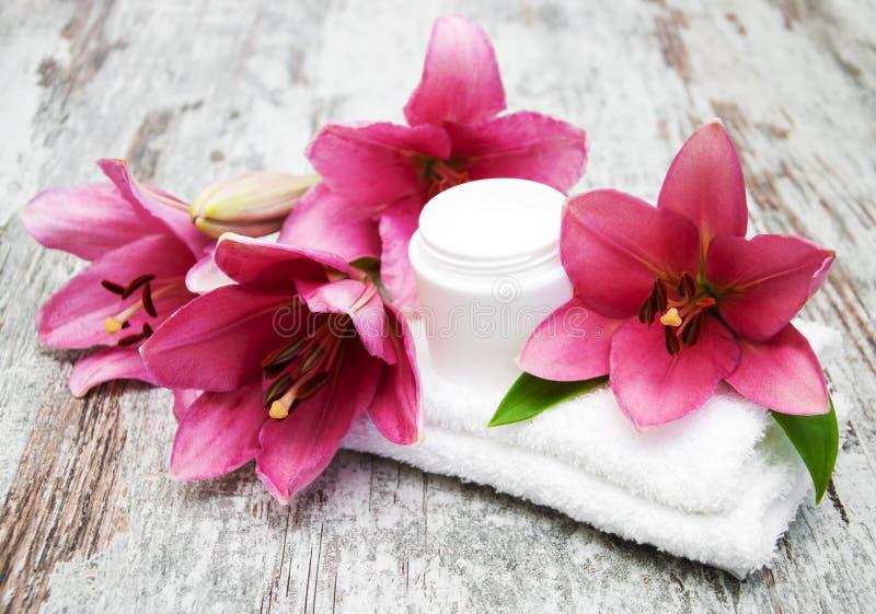 Crema cosmetica e fiore rosa del giglio immagine stock