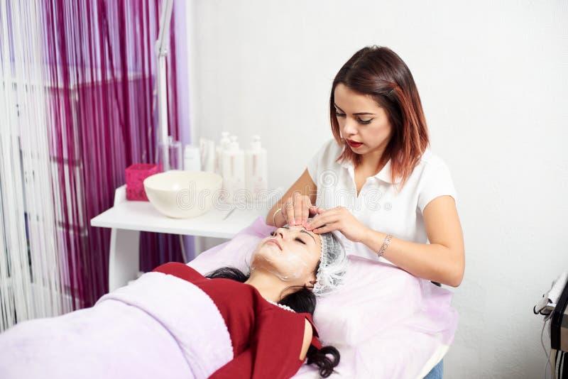 Crema de Applying del Cosmetologist a la cara y a la mujer de los masajes foto de archivo libre de regalías