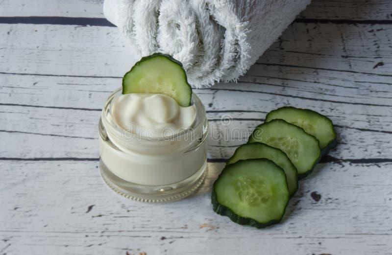 Crema de cara hecha en casa del pepino con la toalla blanca en un fondo de madera blanco fotos de archivo libres de regalías