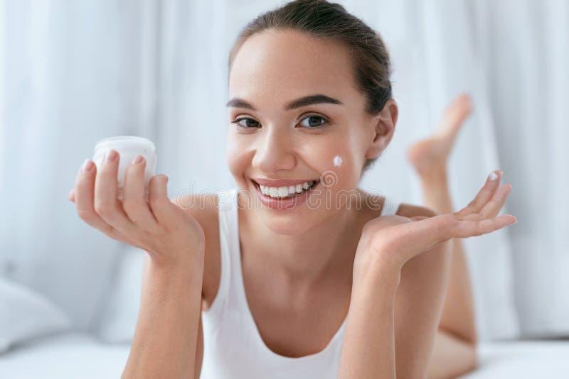 Crema de cara de la belleza Muchacha sonriente hermosa que aplica la crema en piel fotografía de archivo