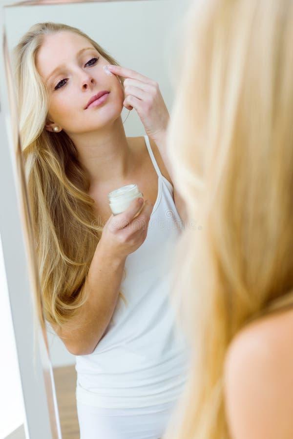 Crema de extensión hermosa de la mujer joven en su cara fotos de archivo