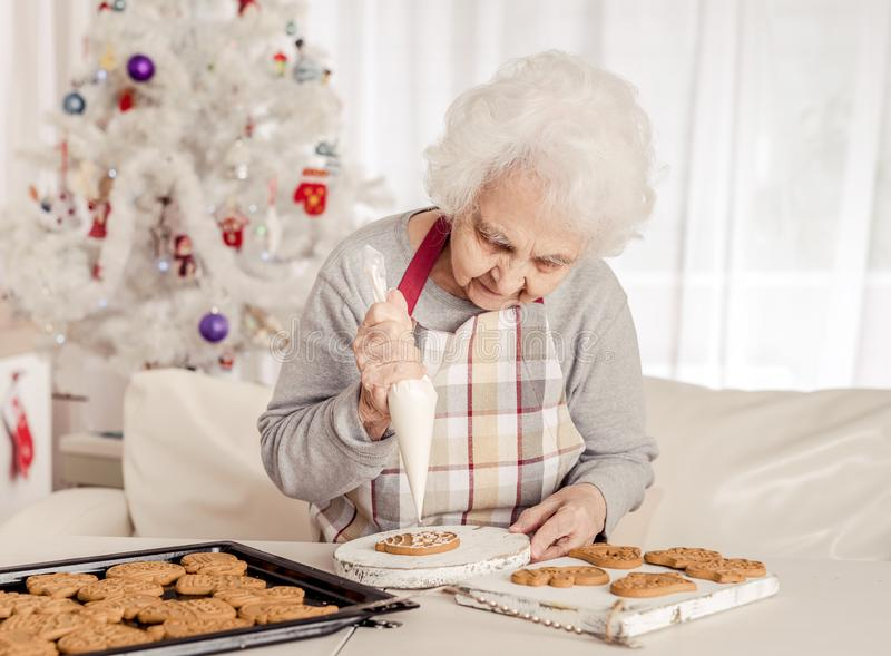 Crema de impregnación de una más vieja mujer en las galletas de la Navidad fotos de archivo