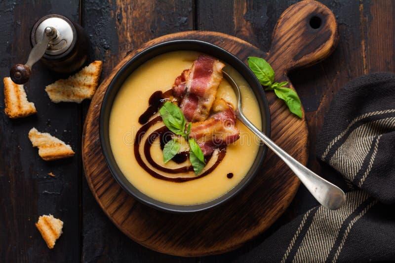 Crema de la sopa de patata con la salsa del tocino y de soja en cuenco negro, en viejo fondo concreto oscuro imagen de archivo libre de regalías