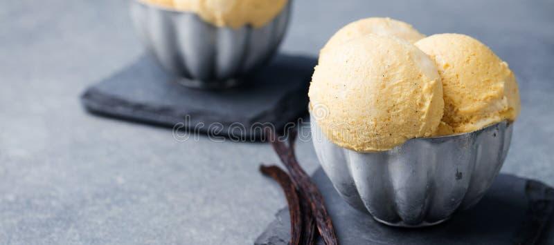 Crema de Vanilla Ice con las vainas de la vainilla en cuenco del vintage del metal Fondo de la pizarra Copie el espacio imágenes de archivo libres de regalías