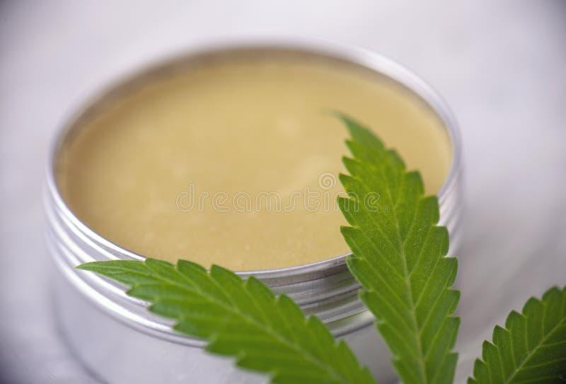Crema del cáñamo del cáñamo con la hoja de la marijuana sobre el fondo blanco foto de archivo