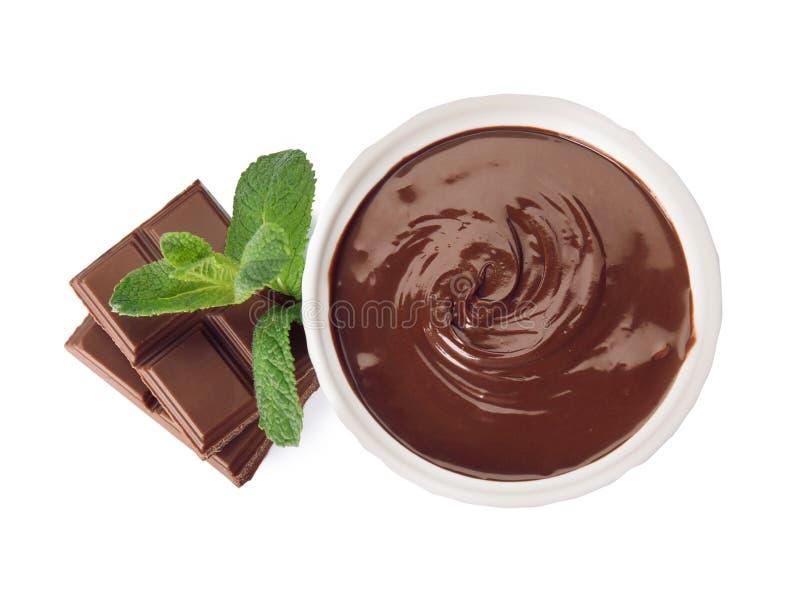 Crema del cioccolato zuccherato in ciotola, pezzi e menta del dessert isolati su bianco fotografie stock libere da diritti