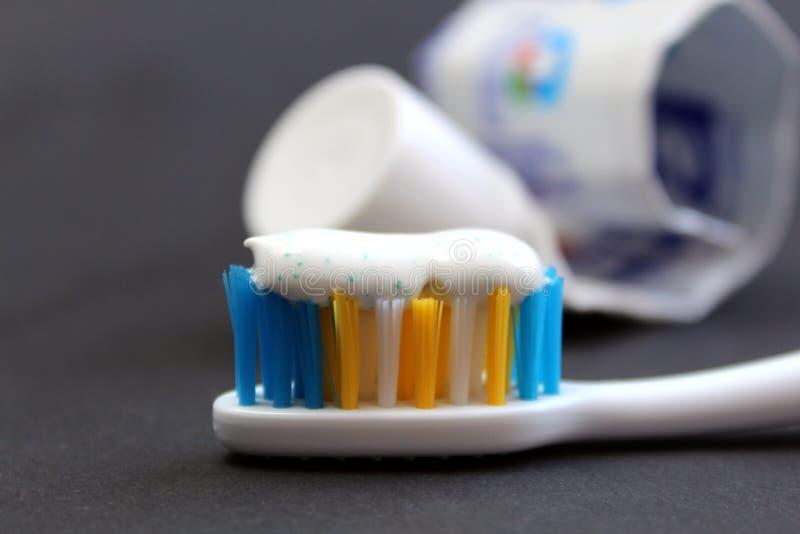 Crema dental y cepillos en un fondo negro imagenes de archivo