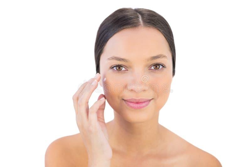 Crema di diffusione sorridente di bellezza della donna sulla sua guancia fotografia stock