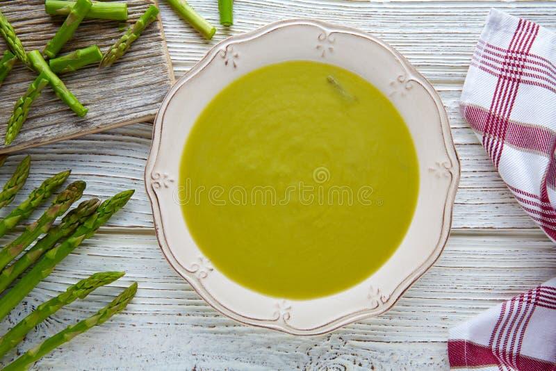 Crema di verde della minestra dell'asparago sulla tavola di legno bianca fotografia stock