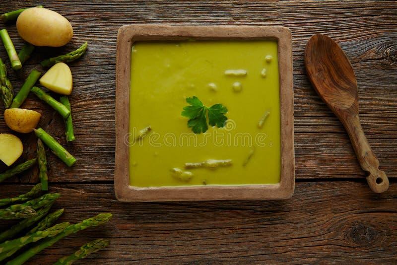 Crema di verde della minestra dell'asparago sulla tavola di legno invecchiata fotografia stock