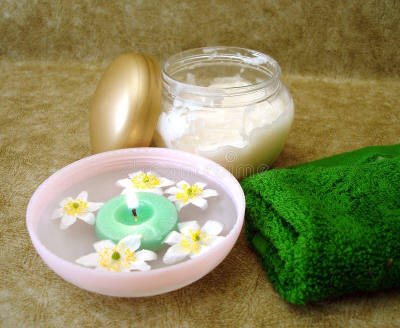 Crema e candela con i fiori immagine stock