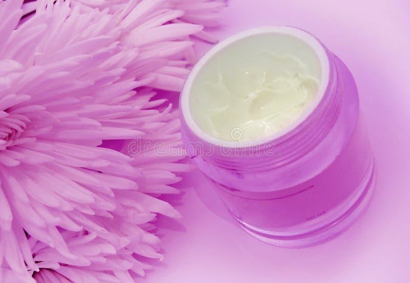 Crema e fiori facciali nel colore rosa fotografie stock libere da diritti